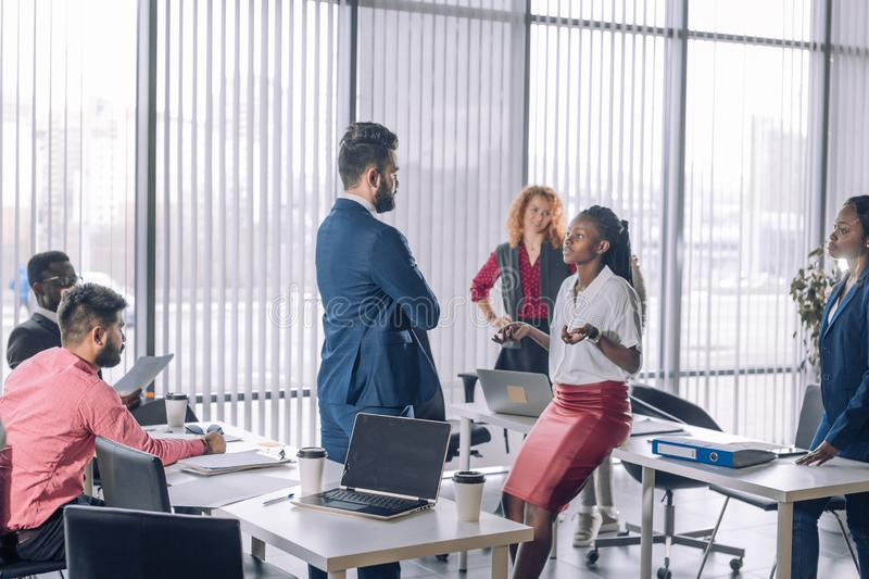 Multiracial business coworkers talking, interacting on workplaces. Backside of caucasian Chief Executive talking with african female employee with other royalty free stock images