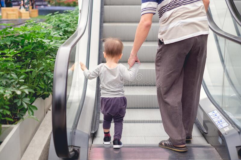 Backside of Cute little Asian 18 months / 1 year old toddler baby boy child and dad holding hands on moving escalator royalty free stock photo