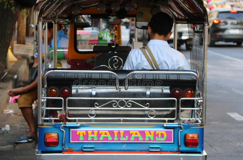 Backside of man driver sitting in his three-wheeled motorized vehicle used as a taxi Tuk Tuk. To wait for passengers beside the royalty free stock images