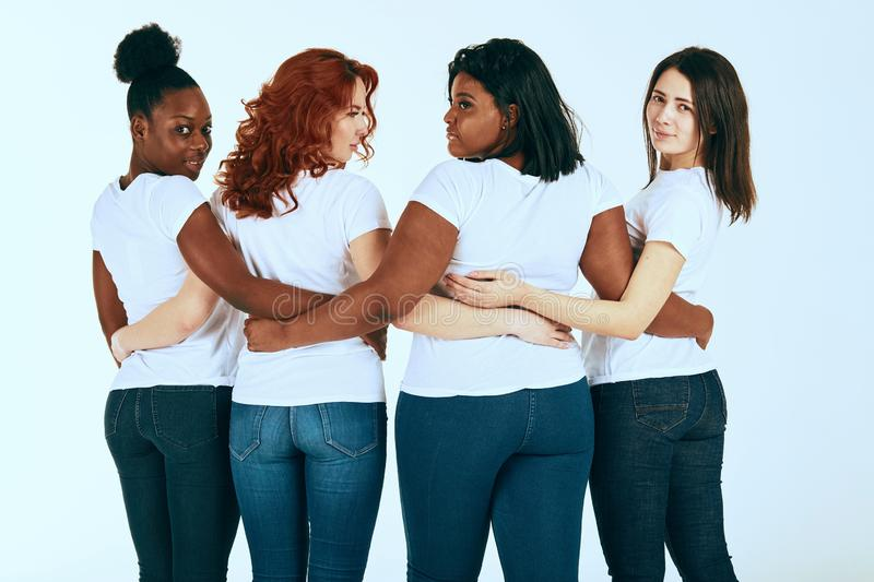 Backside of mixed race group of women in casuals looking happy together on white stock photos