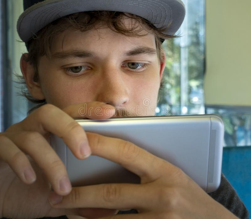 Backside Of A Smartphone, Holded By The Hand Of A Teenager In Cap. Boy look in cellphone stock photos
