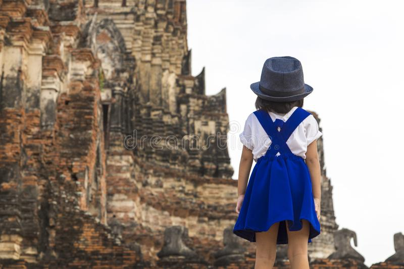 Backside of traveler kid go to travel at ancient Thai temple. royalty free stock photo