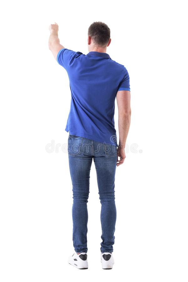 Backside view of casual adult man showing way or pushing interactive touch screen button with left hand. stock photography