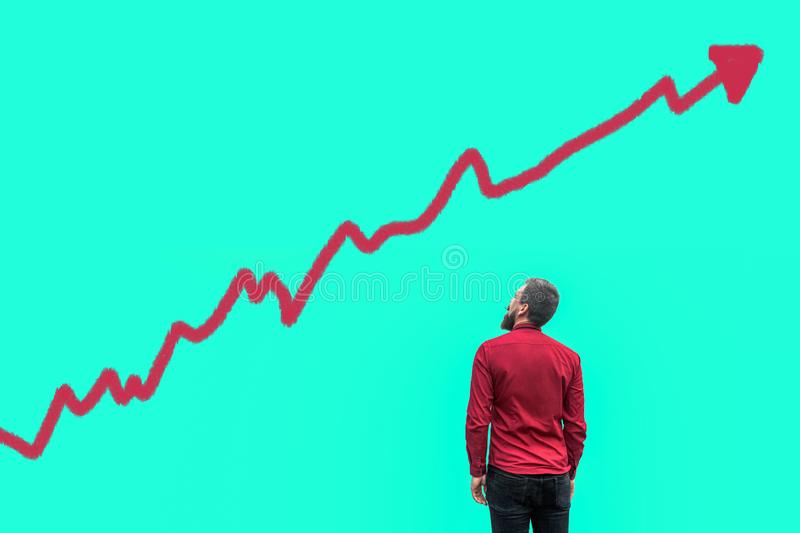 Backside of young bearded handsome businessman in red shirt standing and looking at growing graph chart analysis diagram drawed on stock photos