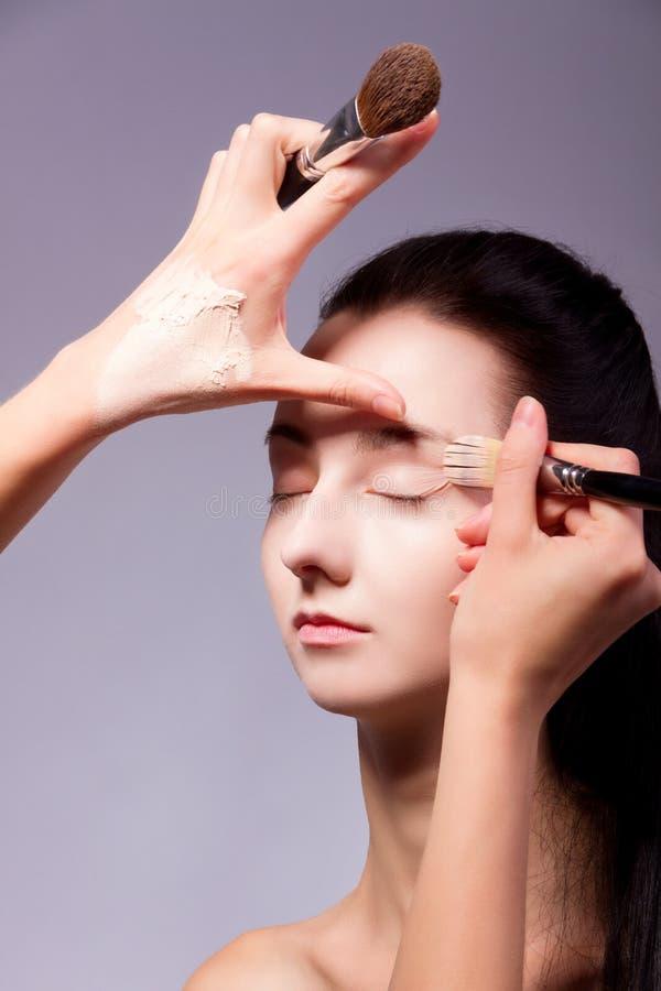 backstabbing Makeupprocess med makeuphjälpmedel arkivfoto