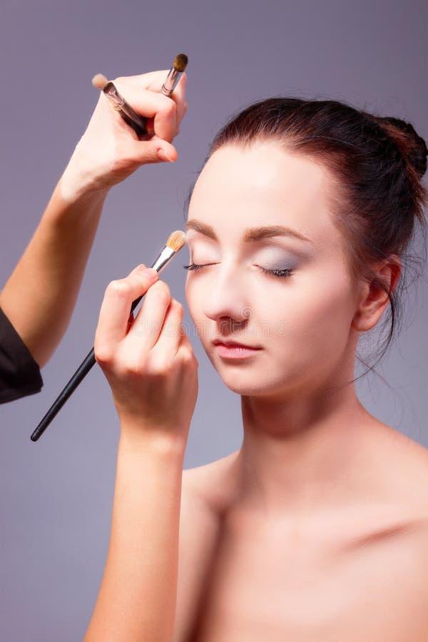 backstabbing Makeupprocess med makeuphjälpmedel arkivbilder
