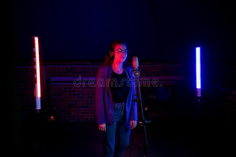 backstage Une jeune femme en verres se tenant prêt le microphone dans l'éclairage au néon photographie stock