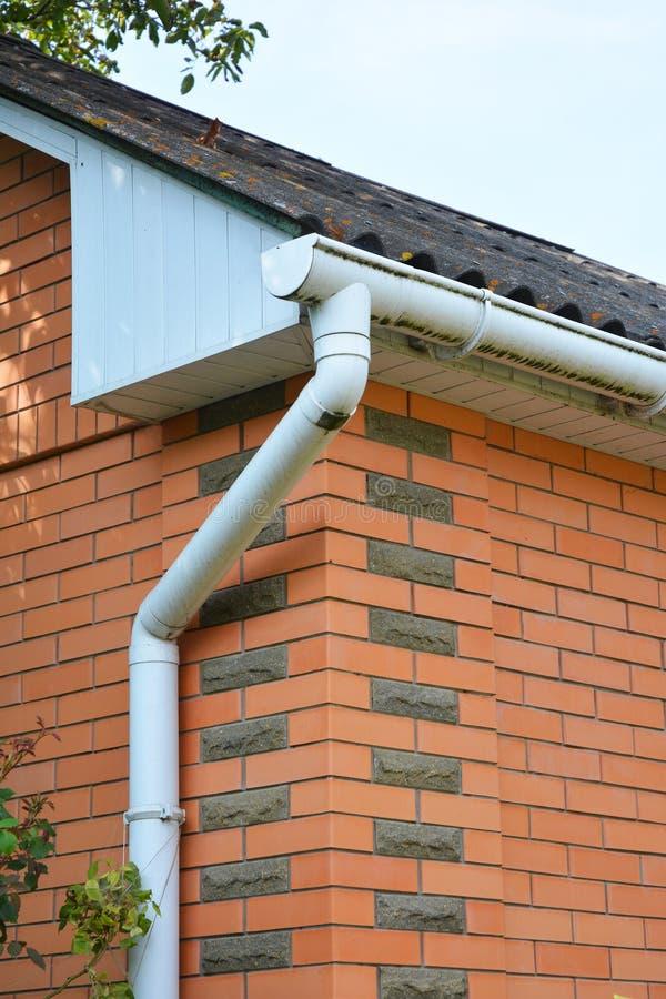 Backsteinhaus-Regen-Gossen-Rohrleitung im Freien Haupt- Guttering, Gossen, Plastik-Guttering-System, Guttering u. Abflussrohr-Äuß lizenzfreies stockbild
