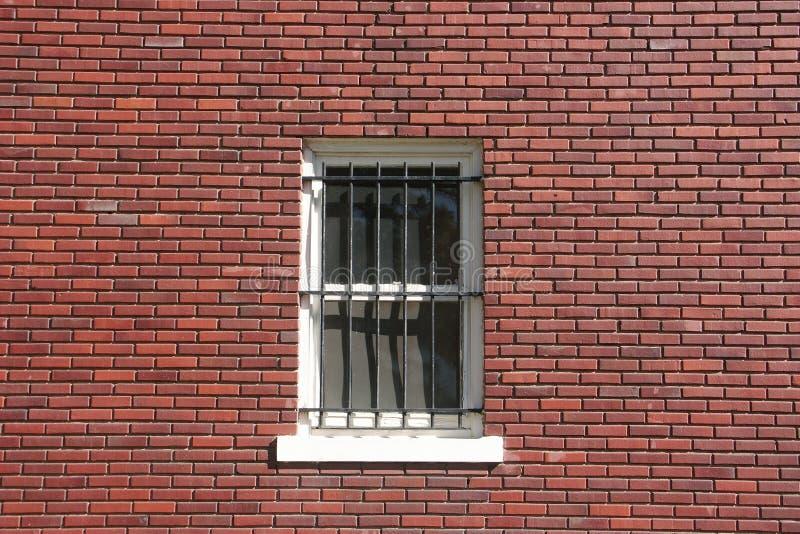 Backsteinmauer, Fenster und Stäbe lizenzfreie stockbilder