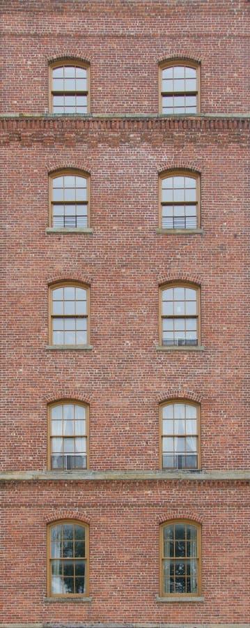 Backsteinmauer mit Bogenfenstern stockfotos
