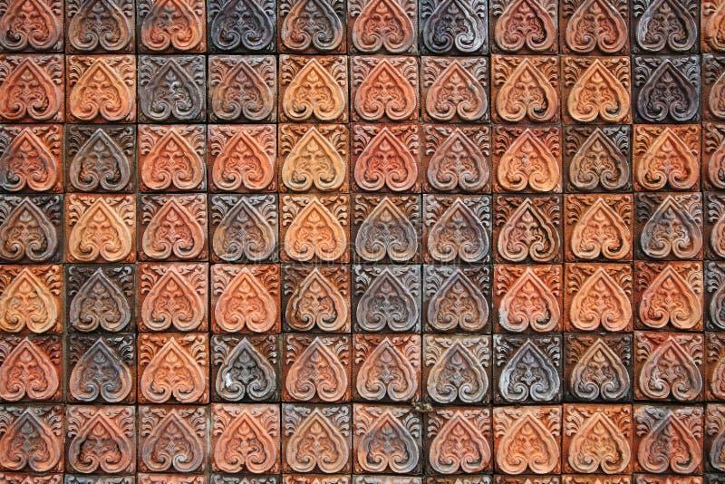 Backsteinmauer mit dem Blumenblattschnitzen stockfotografie