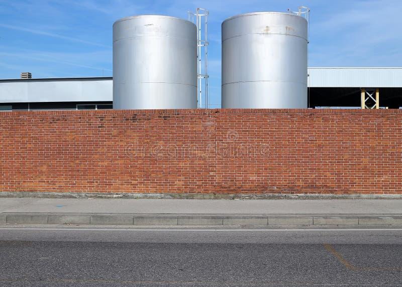 Backsteinmauer mit einem konkreten Bürgersteig und einer Asphaltstraße in der Front Behälter für Flüssigkeit hinten lizenzfreies stockfoto