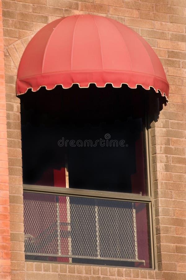 Backsteinmauer und ein Fenster mit roter Markise lizenzfreies stockfoto