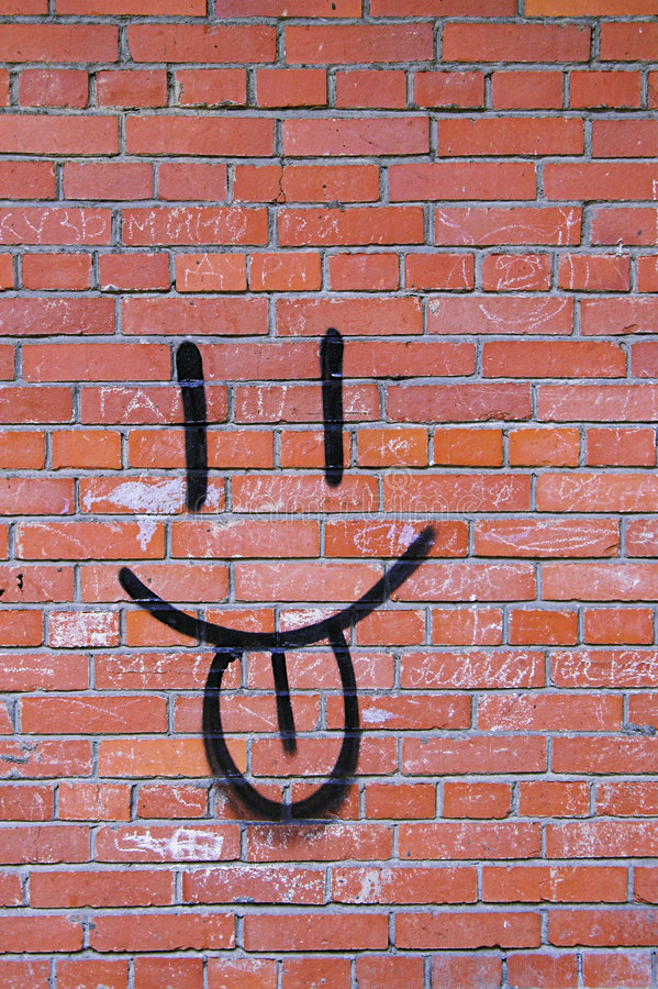 Backsteinmauer-und Lächeln-Graffiti stockbild