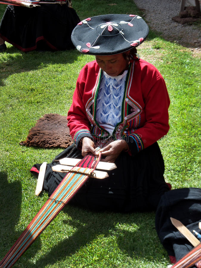 Backstrap Weaver. A woman of the Chinchero Weaving Cooperative in Peru demonstrating traditional weaving techniques with handmade yarns using a backstrap loom stock images