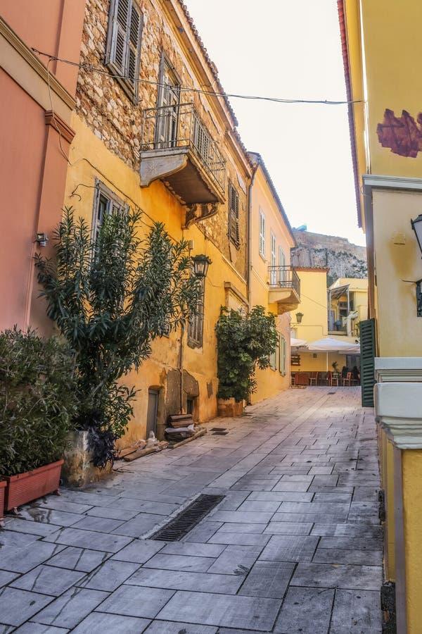 Backstreet przyglądający w górę ściany akropol z plenerowymi kawiarniami w odległości przy Ateny zdjęcie royalty free