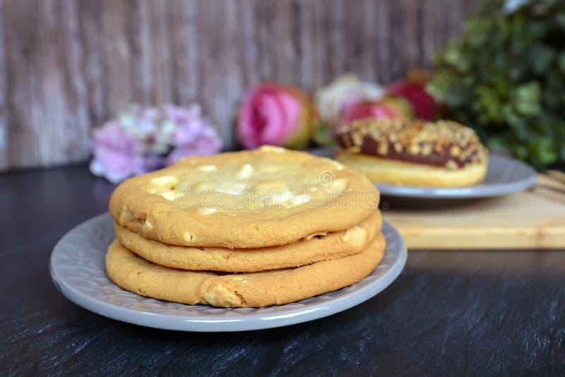 Backte das köstliche Schauen drei nach Hause die weißen Schokoladensplitterplätzchen, die auf einer Platte mit Gebäck im Hintergr stockfoto