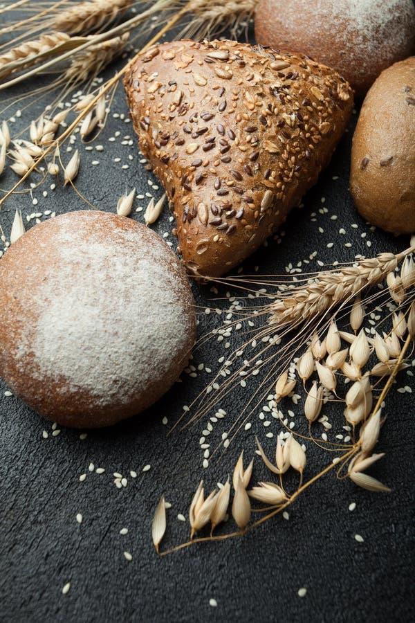 Backte frisch heißes schwarzes Kornbrot, eine ländliche Bäckerei Weizenähren auf einem schwarzen Hintergrund, zerstreuter indisch lizenzfreies stockfoto