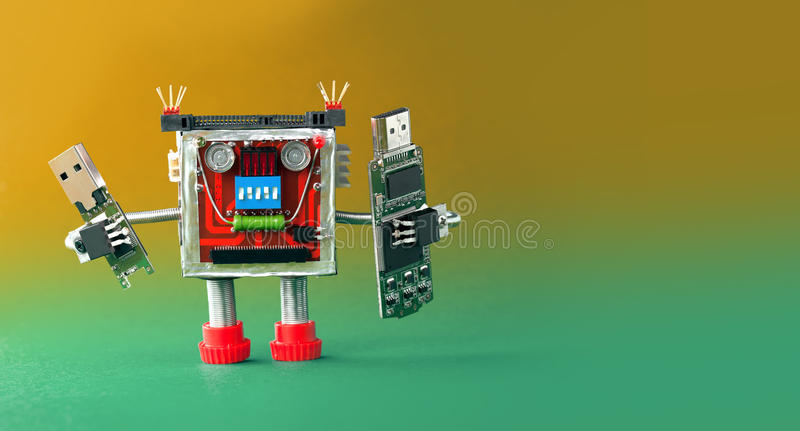 Backup storage information concept. Robot with portable devices usb flash stick. Macro, green yellow gradient background.  royalty free stock image