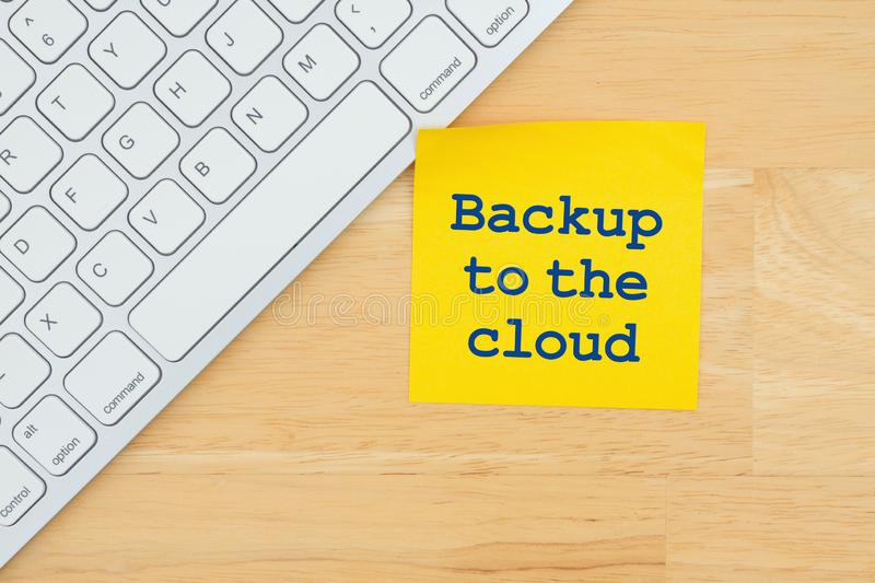 Backup to the cloud on a sticky note with a keyboard. On a desk royalty free stock images