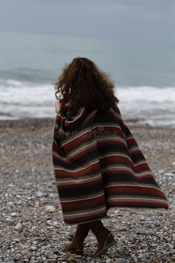 backview πορτρέτο της ευτυχούς γυναίκας brunette στην παραλία που φορά poncho στοκ φωτογραφίες