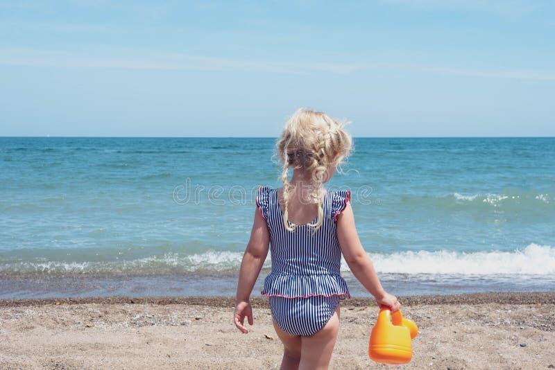 Backview маленькой девочки играя на пляже стоковое изображение