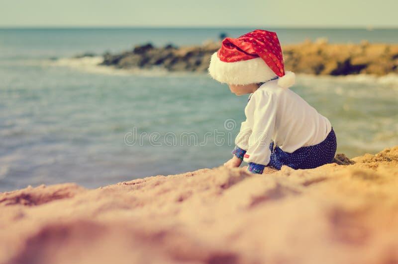 Backview маленького ребенка в шляпе Санты на солнечном стоковое изображение rf