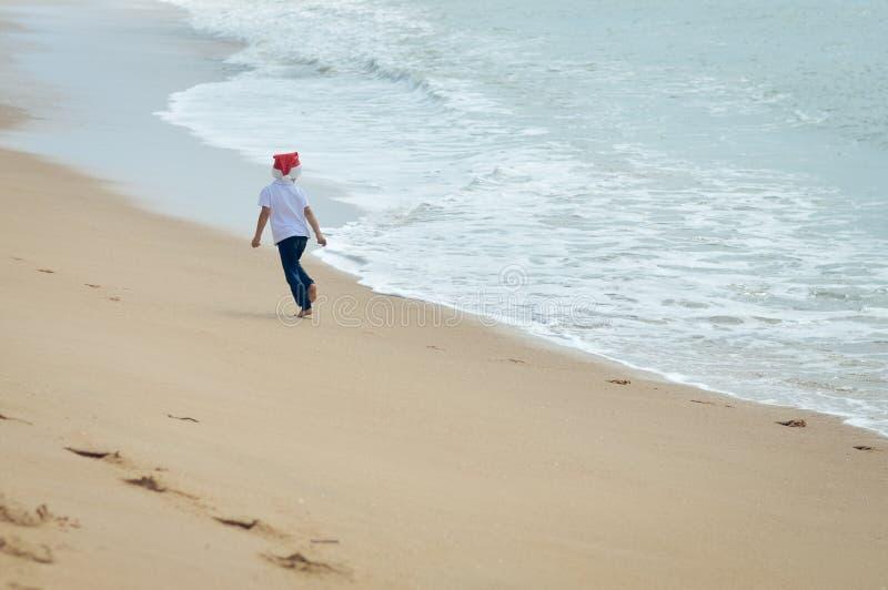 Backview ребенк в шляпе Санты бежать на солнечном стоковые изображения