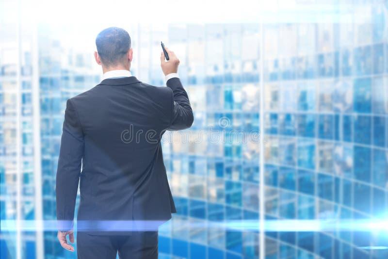 Backview сочинительства бизнесмена на виртуальном экране стоковая фотография rf