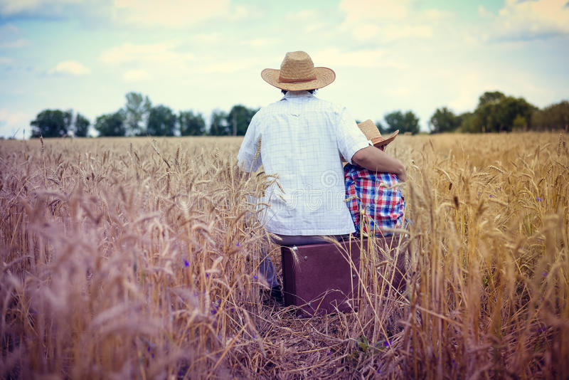 Backview счастливой семьи сидя на старом чемодане стоковое фото