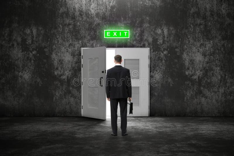 Backview av affärsmannen med fallet för en öppen dörr till en ljusare framtid royaltyfria foton