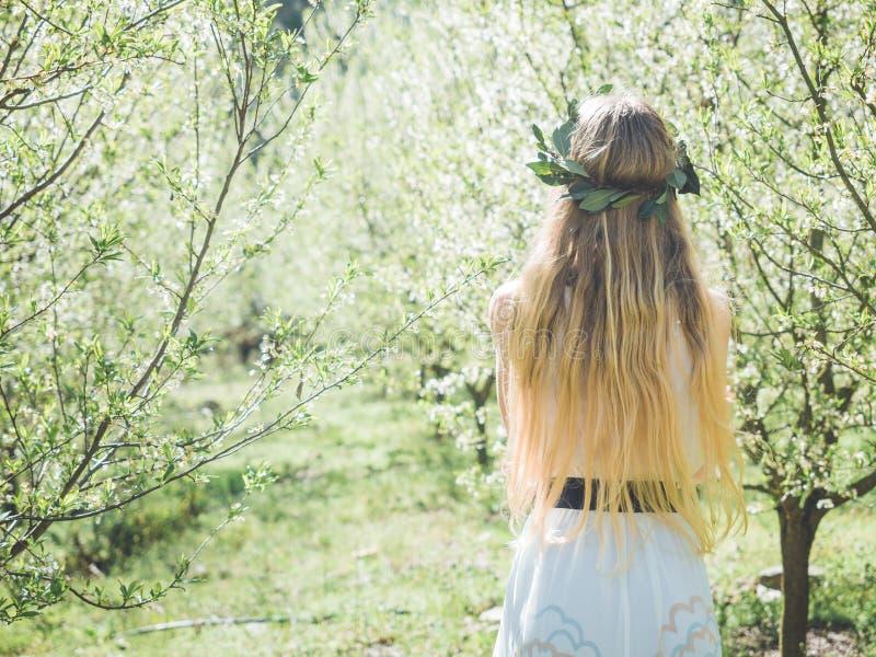 Backview av den unga härliga kvinnan i vårblomningträd royaltyfria bilder