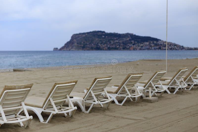 Backview av vita sunbeds på den sandiga stranden arkivfoton