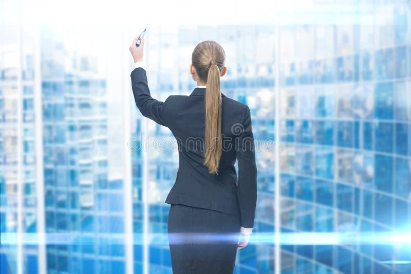 Backview da escrita da mulher de negócios na tela azul fotos de stock