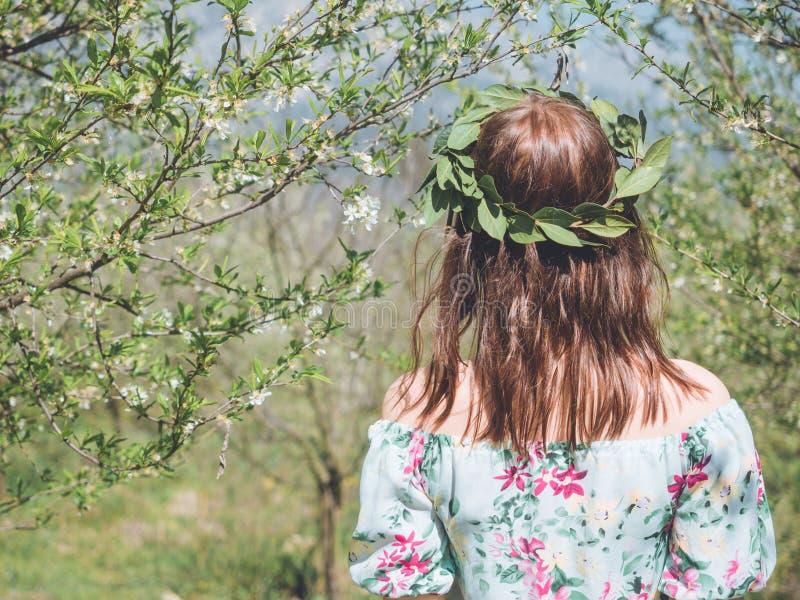 Backview de la mujer hermosa joven en árboles del flor de la primavera imagenes de archivo