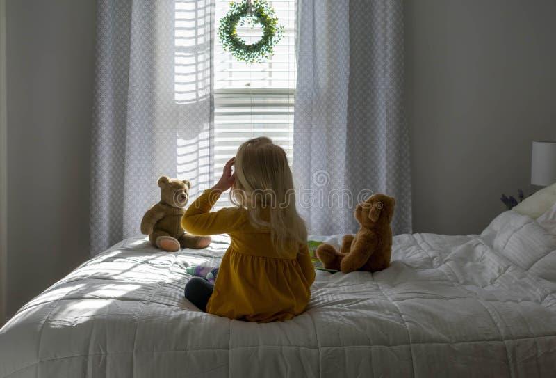 Backview della bambina che si siede sul letto che guarda fuori la finestra fotografie stock