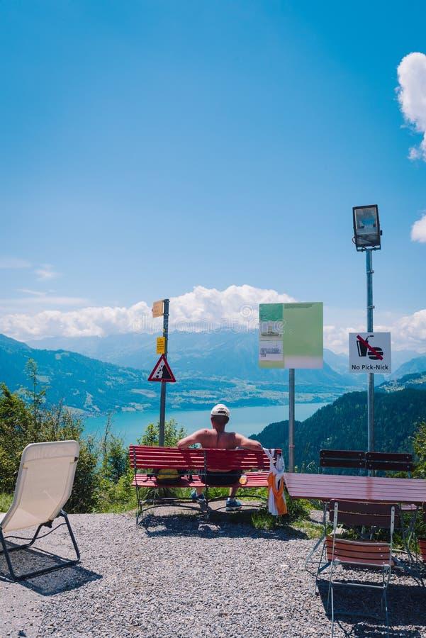 Backview do ancião senta-se na cadeira de madeira vermelha imagem de stock