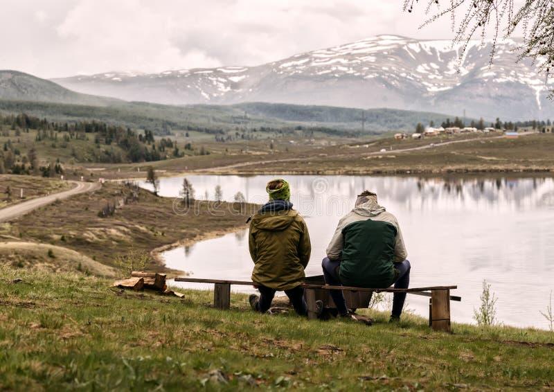 Backview dwa dorosłego faceta sitts na ławce i wydawać spojrzeniem wokoło na pięknie halny jezioro czas, zdjęcie royalty free