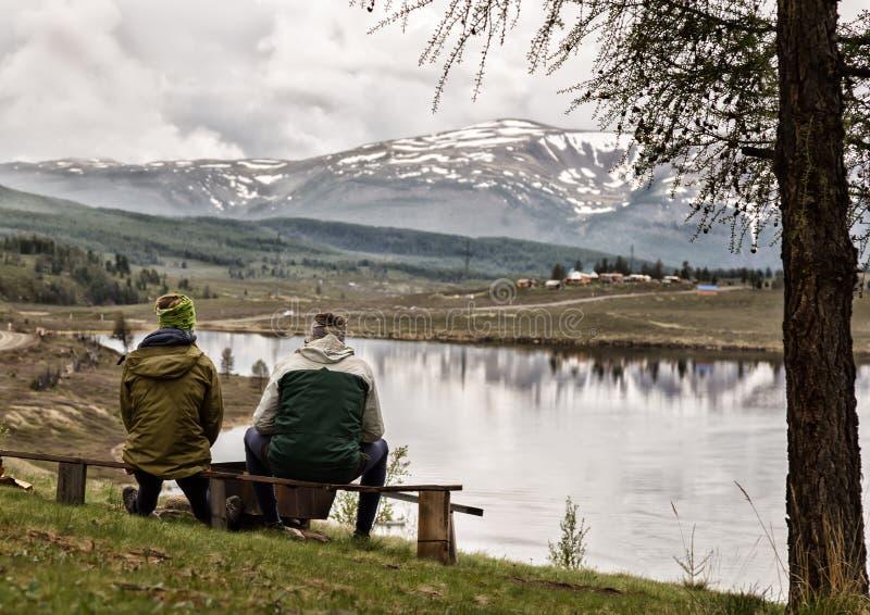 Backview dwa dorosłego faceta sitts na ławce i wydawać spojrzeniem wokoło na pięknie halny jezioro czas, zdjęcia royalty free
