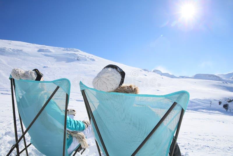 Backview eines Paares, das Sonne auf Ski nimmt, neigt sich stockfotos
