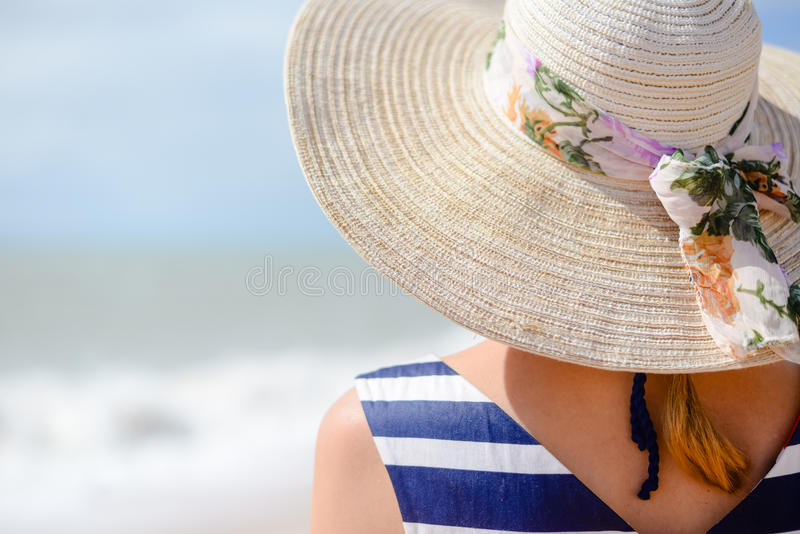 Backview of elegant young woman in straw hat on stock image
