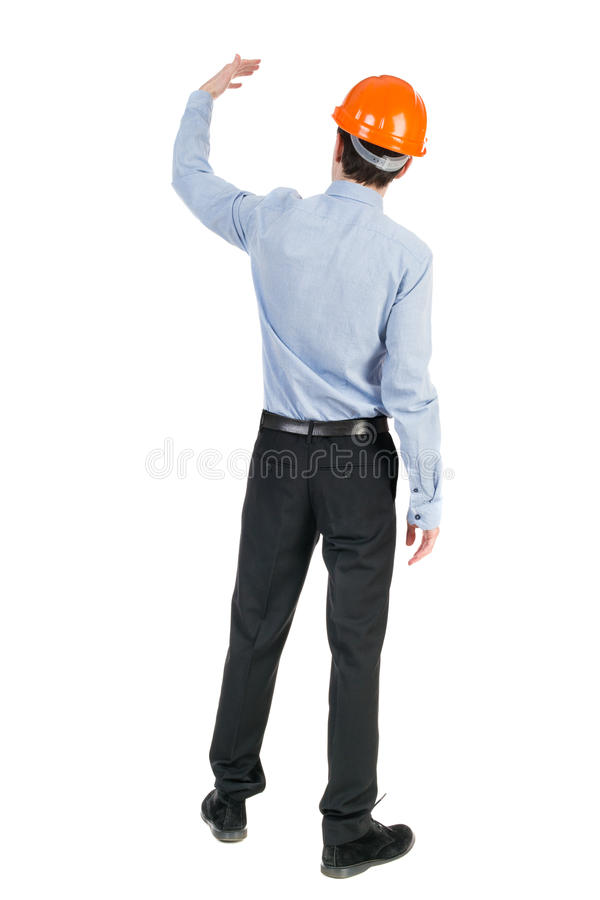 Backview of an engineer in construction helmet stands. Standing stock images