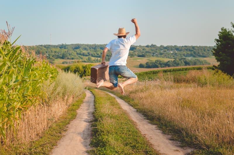 Backview excited человека при чемодан скача дальше стоковые фото