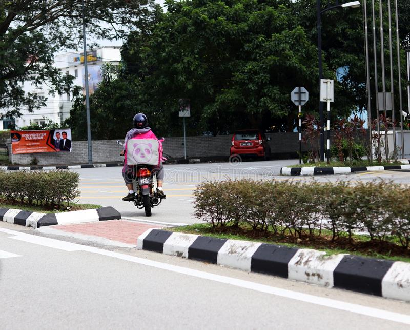 Backview Of A Foodpanda Malay Delivery Woman On Her Motorbike royalty free stock photos