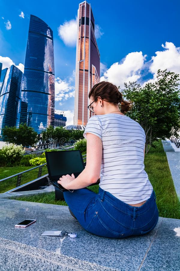 Woman working with notebook laptop out of office. Woman working with notebook laptop out of. Backview of Girl with laptop and smartphone sitting on a railing stock photo