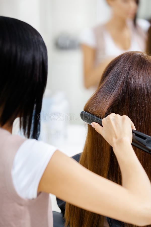 Backview of hairdresser doing hair style for woman royalty free stock photo