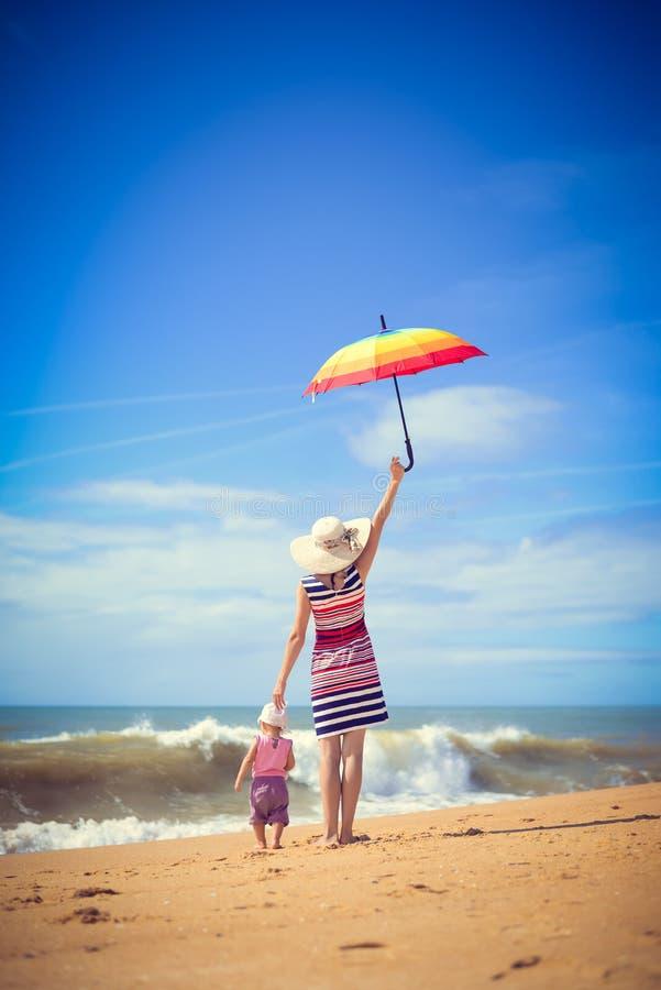 Backview kobiety mienia parasol z dzieckiem zdjęcia stock