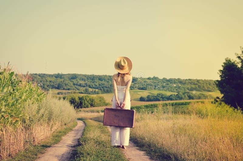 Backview podniecająca młoda kobieta z walizką obrazy stock