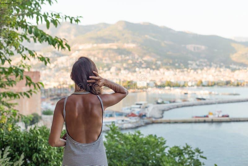 Backview-Porträt der Sitzfrau die Ansicht der Bucht von A genießend stockfotografie