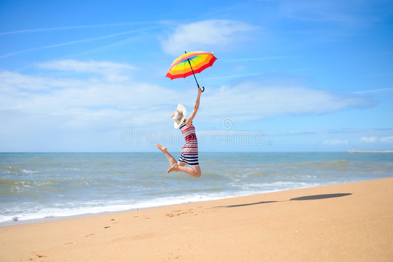Download Backview Of Pretty Woman Jumping With Umbrella On Stock Image - Image of female, ocean: 62326117